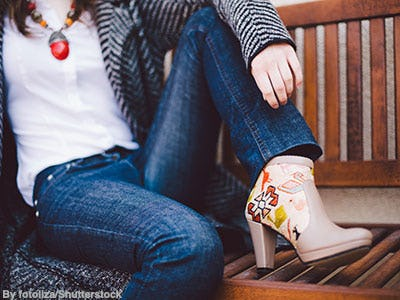 Woman sitting on bench wearing bootcut denim and colorful, southwestern style embroidered taupe booties.