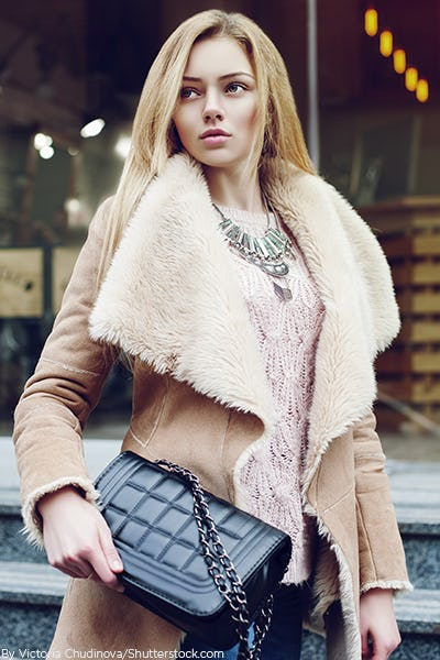 Young woman wearing a light pink knit sweater with a tan coat and a large silver statement jeweled necklace