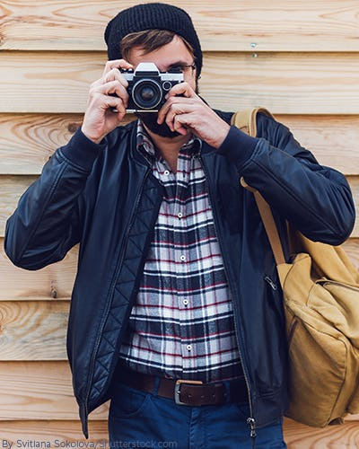 Young fashionable man wearing a navy plaid shirt with a navy bomber and dark denim holding a camera and brown backpack