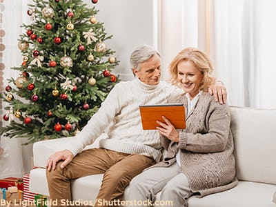 Woman looking at tablet with her husband on Christmas day.