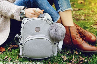 Fashionable grey leather backpack with grey pom-pom.