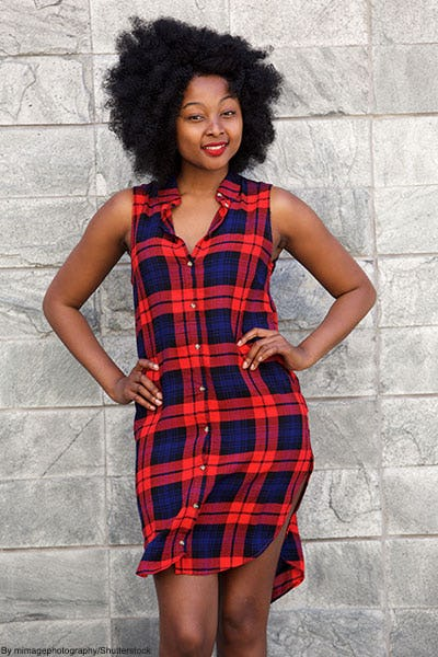 Woman posing in front of gray rock wall wearing a red and blue tartan shirtdress.