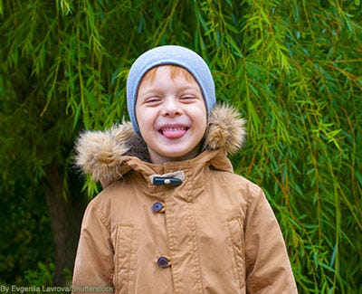 Cute little boy wearing a parka-style anorak and a beanie hat.