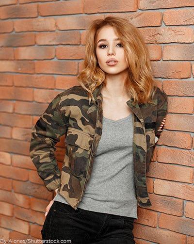 Woman wearing camo bomber jacket.