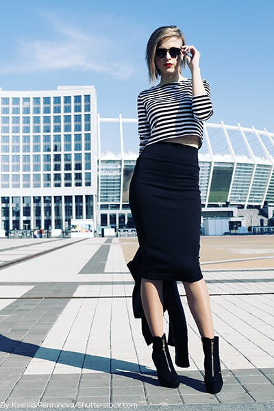 Young blonde woman wearing a black and white stripe crop top and black pencil skirt.