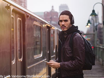 Man waiting for train with headphones and and phone
