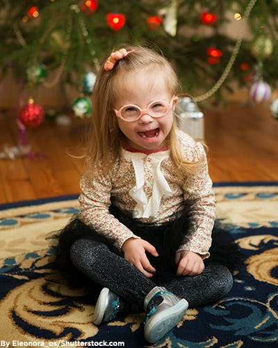 Little girl wearing a floral print ruffled top and black tutu in front of a Christmas tree.
