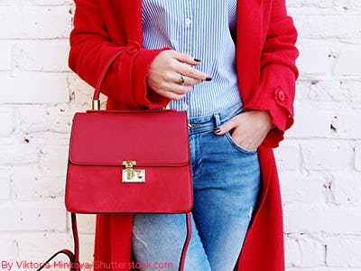 Woman carrying a bright structured red handbag