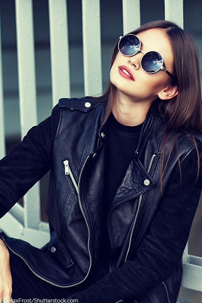 Young fashionable girl wearing a black moto jacket and sunnies