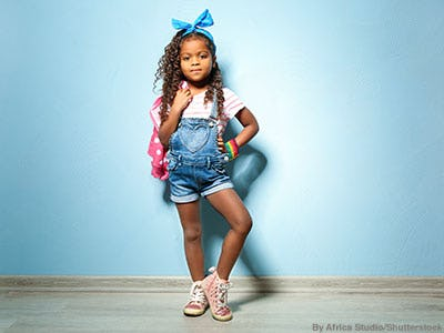 Stylish little girl wearing denim shortalls, a pink backpack, blue hairbow, and pink metallic high-top sneakers.