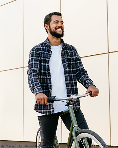 Young man on a bike wearing a navy plaid shirt open with a white t shirt underneath