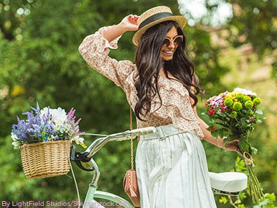 Young brunette haired women wearing a floral print blouse and mint skirt leaning against a bike